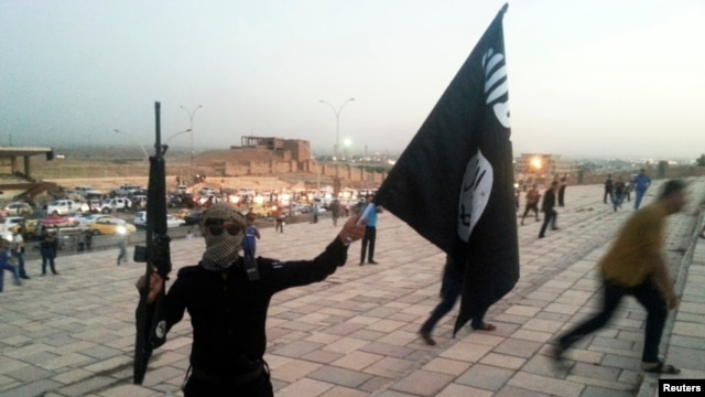 An armed fighter of the Islamic State of Iraq and the Levant waves an ISIL flag in the city of Mosul, Iraq, June 23, 2014.