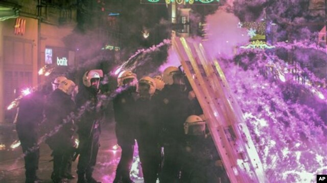 Turkish riot police take cover as they fire water cannons, tear gas at hundreds of demonstrators marching on Taksim Square, Istanbul, Feb. 8, 2014.