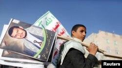 ARSIP – Seorang pendukung membawa poster bergambar pemimpin Houthi, Abdel-Malek al-Houthi selama pawai akbar di Sana'a, Yaman (foto: REUTERS/Khaled Abdullah)