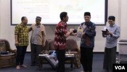 Agus Zainal Mubarok (dua kanan) menerima buku dari Jemaat Ahmadiyah Indonesia (JAI) usai diskusi di Aula Muhahari, Bandung, Senin, 13 Mei 2019. Sementara Ridwan Buton (kedua kiri) nampak berbincang dengan moderator. (Foto: Rio Tuasikal/VOA)