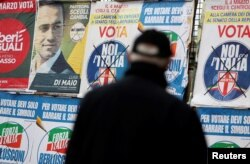 A man looks at electoral posters in Pomigliano D'Arco, near Naples, Italy, Feb. 21, 2018.