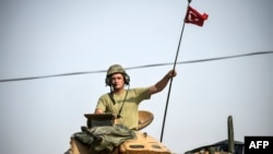 Seorang tentara Turki mengendarai tank di perbatasan Turki dengan Suriah.