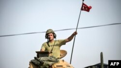 FILE - A soldier gestures as Turkish Army tanks drive to the Syrian-Turkish border town of Jarablus, Aug. 25, 2016