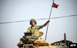 A soldier gestures as Turkish Army tanks drive to the Syrian-Turkish border town of Jarablus, Aug. 25, 2016