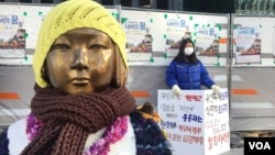 University student Kim So-min, 21, stands in protest outside the Japanese Embassy in Seoul near a bronze statue of a young Korean girl, a reminder of Japan's World War II comfort women. (B. Harrison/VOA )