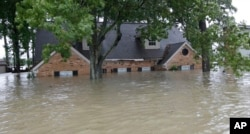 A home is shown as floodwaters from Tropical Storm Harvey rise, Aug. 28, 2017, in Spring, Texas.