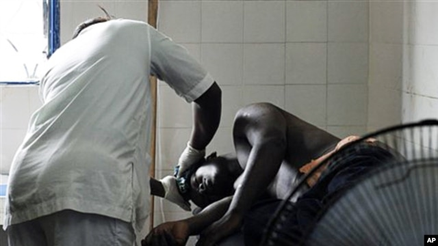 A man receiving treatment at a health clinic after being shot in the hip by security forces loyal to Laurent Gbagbo in the Anyama suburb of Abidjan, March 12, 2011