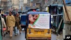 Sebuah becak mobil dengan poster yang mengiklankan kampanye polio melewati pasar di Peshawar, Pakistan. Pakistan. (Foto: AP)