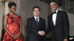President Barack Obama and first lady Michelle Obama greet Chinese President Hu Jintao at the Grand Staircase as they arrive for a state dinner at the White House in Washington, Jan. 19, 2011.