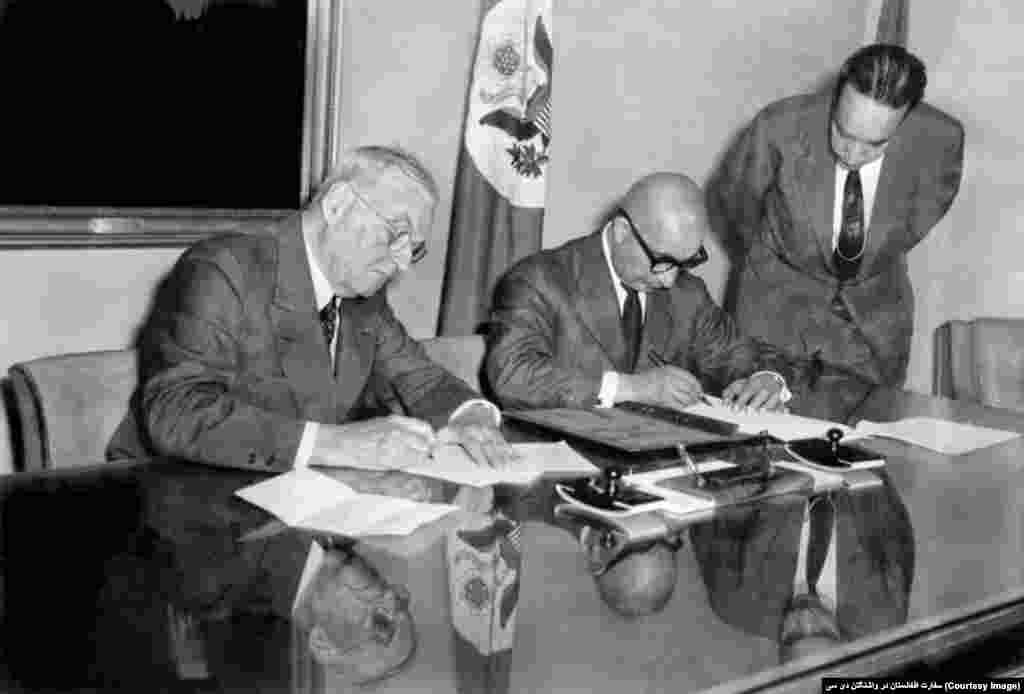 محمد داوود خان صدر اعظم پیشین افغانستان حین امضای توافقنامه تبادله فرهنگی با جان فوستر دلس وزیر خارجۀ پیشین ایالات متحده، سال ۱۹۵۸ میلادی