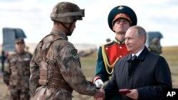 """俄罗斯总统普京(右)在中俄边界附近举行的""""东方-2018""""战略军演后给一名中国军人颁发勋章。(2018年9月13日)"""
