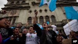 Demonstrators wave Guatemalan flags as they celebrate that Congress voted to withdraw President Otto Perez Molina's immunity from prosecution, in Guatemala City, Tuesday, Sep. 1, 2015.