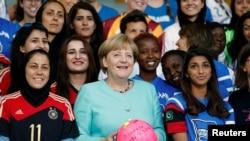"""La chancelière allemande Angela Merkel et l'équipe féminine internationale de football du projet """"Discover Football"""", à la chancellerie à Berlin, en Allemagne, le 1er Septembre 2016. REUTERS / Hannibal Hanschke - RTX2NT1K"""