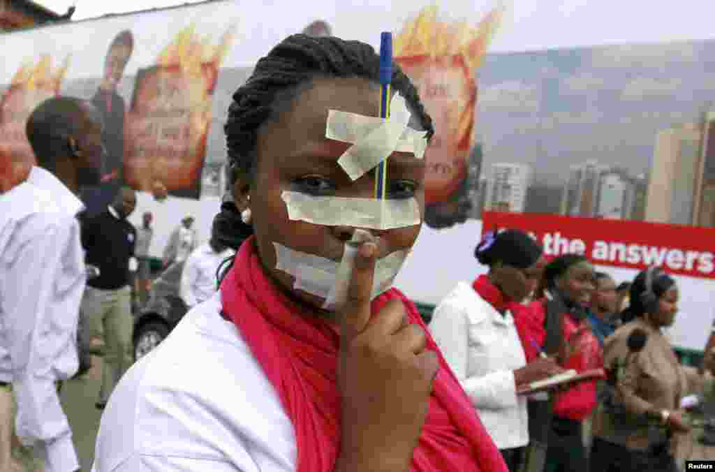 A Kenyan journalist participates in a protest with tape over her mouth and a pen on her forehead along the streets of the capital Nairobi. Members of the media marched in a peaceful protest to denounce the new draconian laws tabled by parliament.