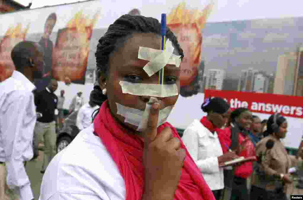 케냐 나이로비의 언론인들이 정부 규제에 항의하는 평화시위를 벌인 가운데, 한 기자가 테입으로 입을 막고 머리에는 펜을 붙이고 시위에 참가했다.