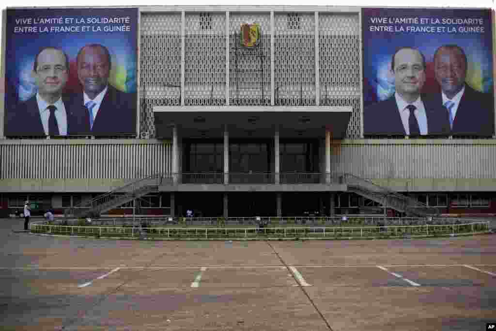 Giant posters featuring French President Francois Hollande and his Guinean counterpart Alpha Conde are displayed on the facade of the People's Palace in Conakry, Guinea, Wednesday, Nov. 26, 2014.