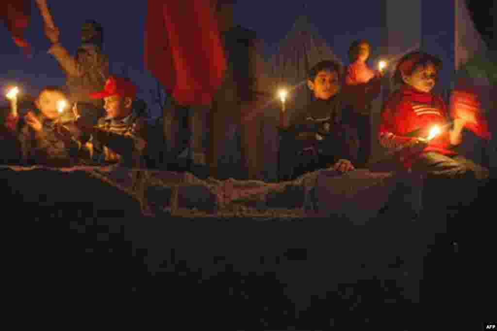 Palestinian children hold candles during a demonstration organized by the Popular Front for the Liberation of Palestine (PFLP), marking the 2nd anniversary of the Israel-Gaza war, in the Jebaliya refugee camp, northern Gaza Strip, Monday, Dec. 27, 2010. I