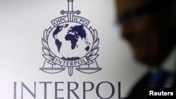 FILE - A man passes an Interpol logo in Singapore.