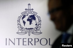 FILE - A man passes an Interpol logo.