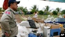 Seorang polisi Kamboja menjaga peralatan pembuat aneka narkoba yang disita dari pinggiran Phnom Penh. (Foto: Dok)
