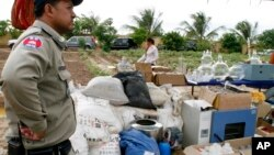 A Cambodian police officer stands next to equipment used to make various drugs, which were seized in raids earlier this year in eastern and southern Cambodia, on the outskirt of Phnom Penh, file photo.