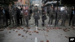 FILE - Riot police stand guard as rioters set fires and throw bricks in Mong Kok district of Hong Kong, Feb. 9, 2016.