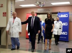 FILE - President Donald Trump and first lady Melania Trump walk with surgeon Dr. John Fildes at the University Medical Center after meeting with victims of the mass shooting in Las Vegas, Oct. 4, 2017.