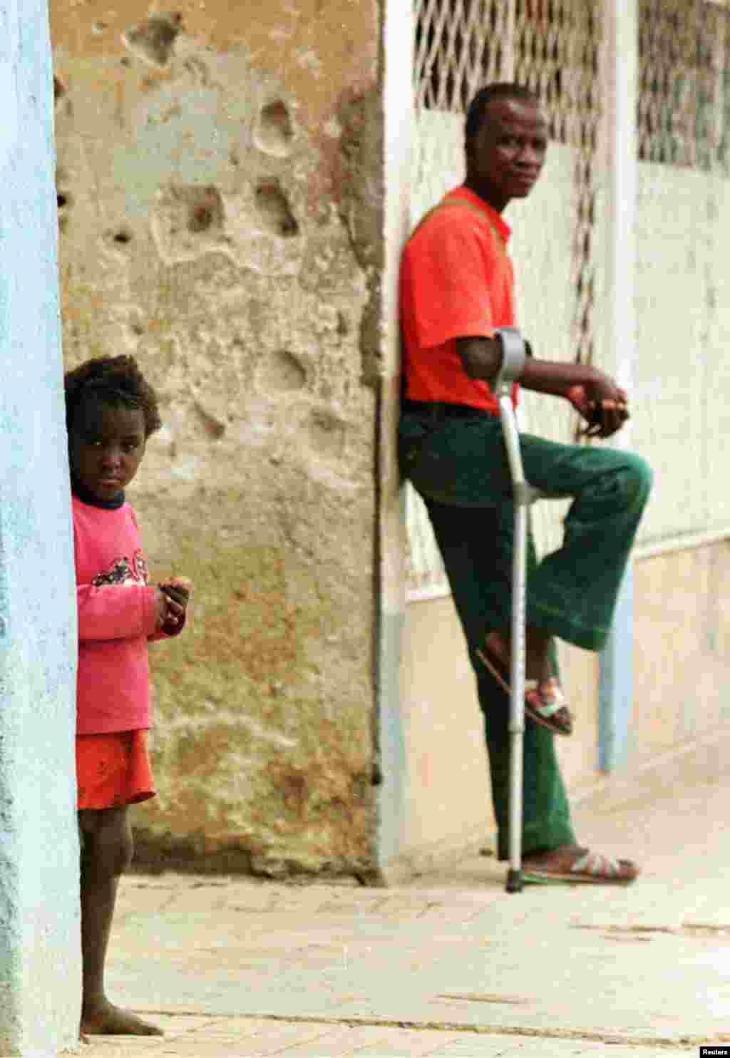 Criança e homem amputado na cidade de Huambo, em fevereiro de 1998