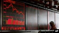 一名男子在北京的一个交易所查看股市行情