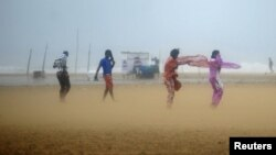 Women shield their faces during strong winds at Marina beach in Chennai, southern India, Oct. 31, 2012.