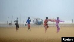 印度南部钦奈地区海滨妇女在大风中蒙盖头脸