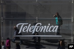 People are reflected in a glass sign of a Telefonica building in Madrid, Spain, May 13, 2017. The Spanish government said several companies including Telefonica had been targeted in ransomware cyberattack that affected the Windows operating system of employees' computers.