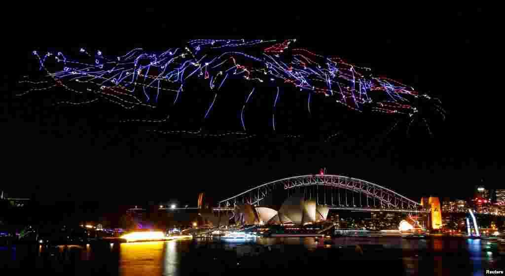 រូបភាពបង្ហាញពីការសម្តែងលើអាកាសនៃយន្តហោះគ្មានមនុស្សបើកចំនួន ១០០ គ្រឿង ដែលមានបំពាក់ភ្លើងពណ៌ពីលើស្ពាន Sydney Harbour Bridge និងអគារ Opera House នៅអំឡុងពេលពិធីបុណ្យភ្លើងពណ៌ Vivid Sydney ក្នុងក្រុងស៊ីដនី ប្រទេសអូស្រ្តាលី។