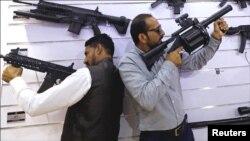 نمائش میں شریک دو افراد جدید ہتھیاروں کے ساتھ 'ایکشن ' میں