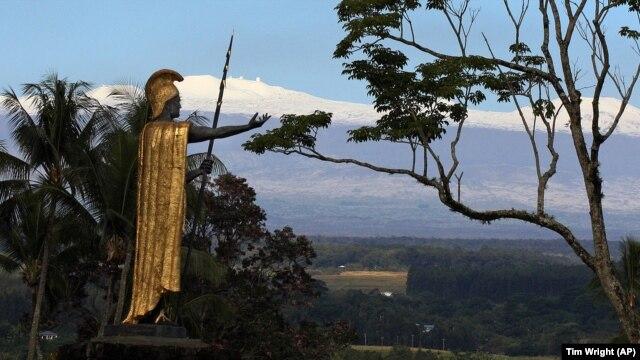 Snow on Mauna Kea is seen Friday Jan. 31, 2014, behind a statue of the Hawaiian King Kamehameha in Hilo, Hawaii.