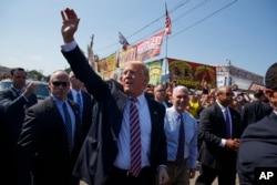 ຜູ້ສະໝັກແຂ່ງຂັນເປັນປະທານາທິບໍດີ ຈາກພັກຣີພັບບລີກັນ ທ່ານ Donald Trump ໂບກມື ຂະນະທີ່ ທ່ານໄດ້ຍ່າງໄປກັບຜູ້ສະໝັກເປັນຮອງປະທານາທິບໍດີ ຄືຜູ້ປົກຄອງລັດ Indiana ຈາກພັກຣີພັບບລີກັນ ທ່ານ Mike Pence, ໃນລະຫວ່າງການຢ້ຽມຢາມ ງານຕະຫຼາດນັດ ຂອງເມືອງ Canfield ຄັ້ງທີ 170, ວັນທີ 5 ກັນຍາ 2016, ໃນລັດ Ohio.