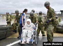 An elderly man in a wheelchair is rescued from a flooded area in Kurashiki, Okayama Prefecture, Japan, July 8, 2018.
