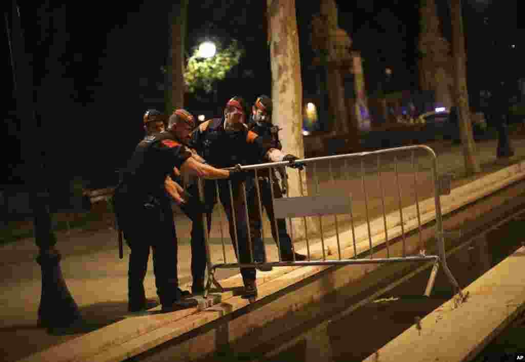 افسران پلیس اسپانیا در حال گذاشتن موانع بیرون از ساختمان پارلمان کاتالونیا در بارسلون