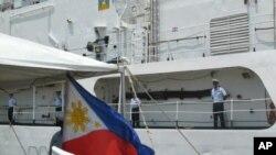 美國海岸警衛隊員於2012年5月12日,在移交儀式上站立在退役巡邏船達拉斯號的甲板上。該船被移交給菲律賓海軍。