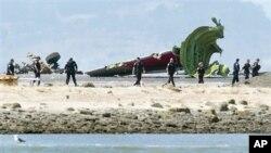 Các nhà điều tra gần hiện trường nơi đuôi và bộ phận hạ cánh của máy bay bị đứt rời thân máy bay Asiana tại sân bay quốc tế San Francisco.