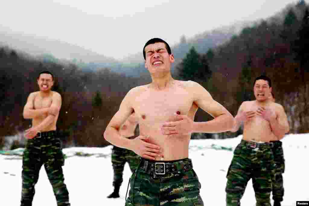 Para anggota pasukan paramiliter China membasuh tubuh mereka dengan salju pada saat latihan fisik musim dingin di Changchun, provinsi Jilin.