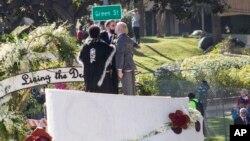 Обри Лутс, Дэнни Леклэр и пастор Альфреда Ланой на вершине платформы в виде свадебного торта.