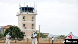 Une équipe médicale nettoie le terrain d'aviation, pour prévenir la propagation de la maladie à coronavirus (COVID-19), à l'aéroport international de Juba, à Juba, au Sud Soudan, le 5 avril 2020.