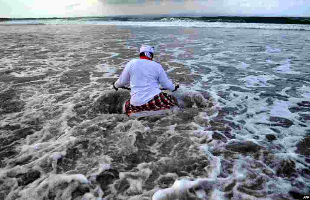 Seorang pria Bali terjun ke laut dalam upacara doa Melasti menjelang hari raya Nyepi, di pantai Petitenget dekat Denpasar.