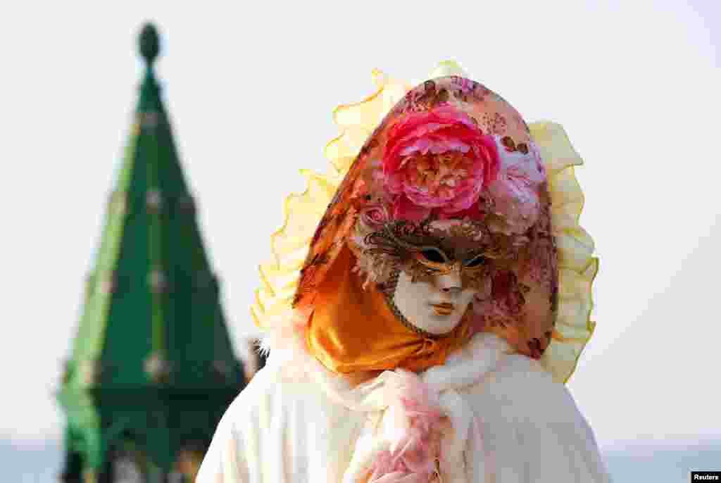អ្នកដើរលេងម្នាក់ថតរូបនៅក្នុងទីលាន Saint Mark's Square ក្នុងពិធីបុណ្យ Carnival នៅក្នុងក្រុង Venice ប្រទេសអ៊ីតាលី កាលពីថ្ងៃទី១៨ ខែកុម្ភៈ ឆ្នាំ២០១៧។