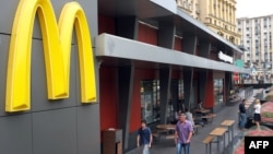 People walk in front of a closed McDonald's restaurant, the first to be opened in the Soviet Union in 1990, in Moscow, August 21, 2014.