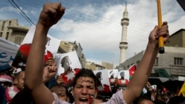 """Demonstrators, one painting his national flag and Arabic that reads """"Muath,"""" chant anti-Islamic State group slogans and carry posters with pictures of slain Jordanian pilot, Lt. Muath al-Kaseasbeh, during an anti-IS group rally in Amman, Jordan, Feb. 6, 2015."""