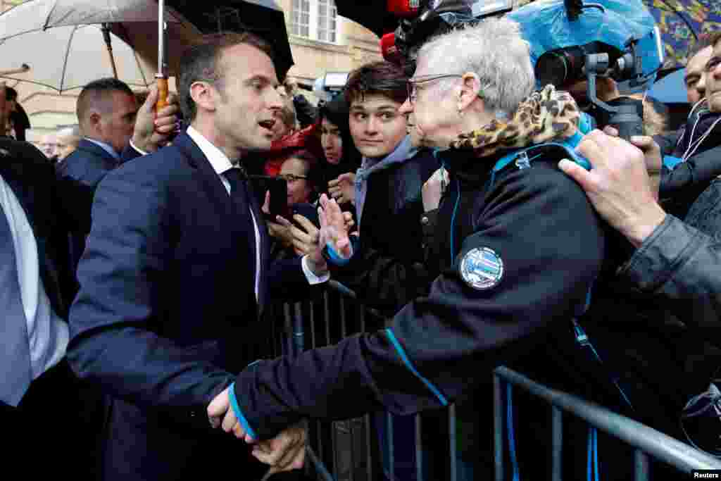 French President Emmanuel Macron talks with a resident at the city hall in Charleville-Mezieres, Eastern France, as part of a World War I commemoration tour.