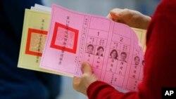 一位台湾民众2016年1月16日在台北一投票站准备填写手中的选票