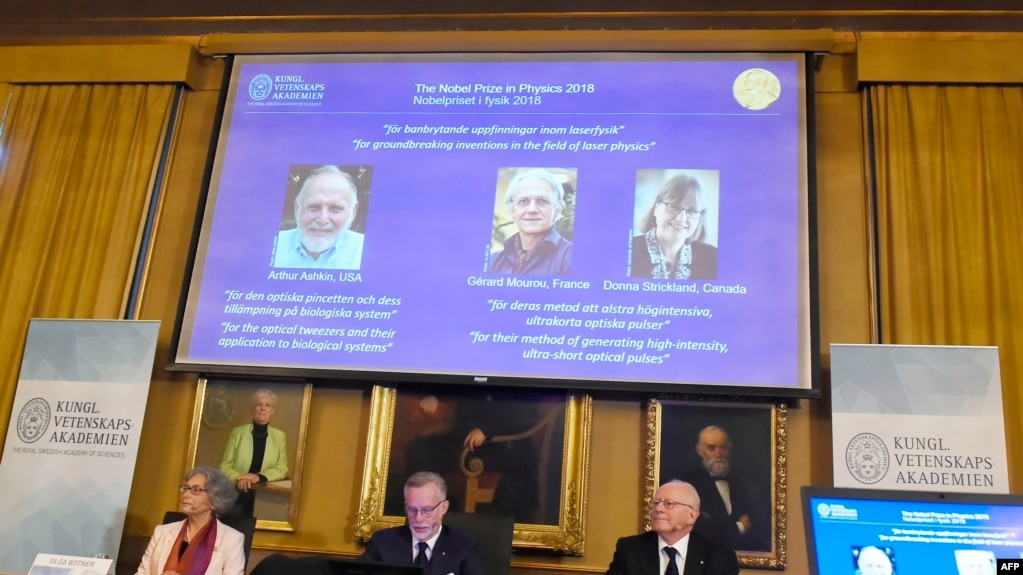 Các thành viên của Ủy ban Nobel Vật lý ngồi trước màn hình trưng bày chân dung các khoa học gia Arthur Ashkin người Mỹ, Gerard Mourou người Pháp và Donna Strickland người Canada trong công bố giải Nobel Vật lý năm 2018.